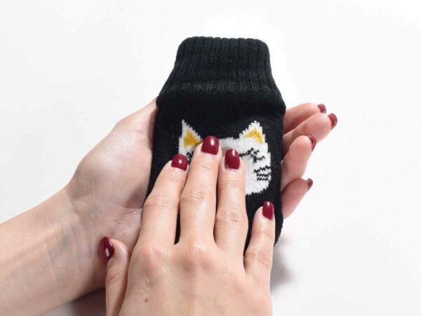 Scaldamani con copertura in maglia decorata con un musetto di gatto, fotografato in mano